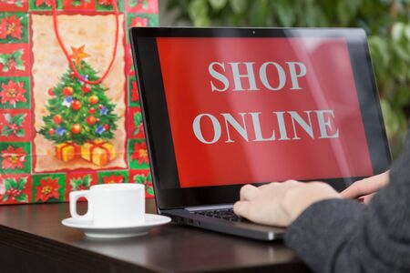 Girl sits at a laptop and makes purchases over the internet on christmas. Fast and easy trading concept