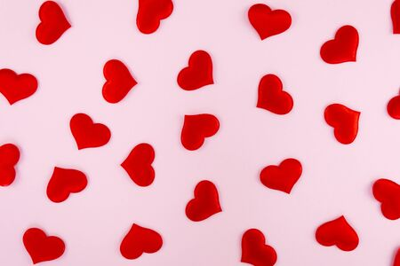 red hearts scattered on a pink background