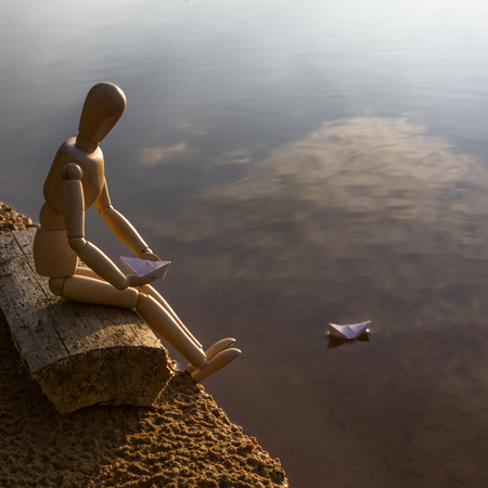 Wooden man is sitting on the beach and launching paper boats