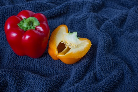 Top veiw of a red pepper and half orange pepper on a blue background