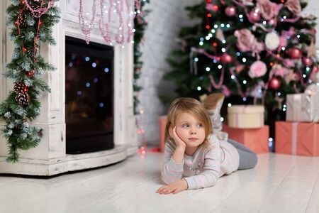Thinking, the cute baby girl touches her face with a thoughtful expression on it, looking at a bunch of colorful gifts. Portrait of a pensive little girl dreaming of a good present for the new year.