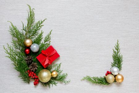 Green branches and Christmas balls. Christmas decor on a light background. New Years gift in a small red box. Reklamní fotografie