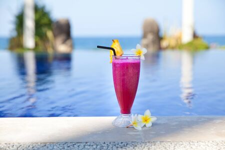 Dragon fruit juice. Hotel rest. Dragon fruit shake. Fresh cocktail and frangipani flowers by the pool. A refreshing drink on the beach.