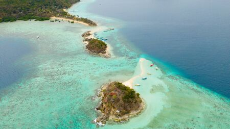 Island with a sand spit and coral reefs. Clear transparent sea near the island Bulog Dos Reklamní fotografie