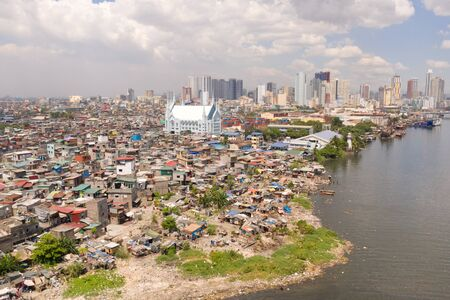 The urban landscape of Manila, with slums and skyscrapers. Sea port and residential areas. The contrast of poor and rich areas. The capital of the Philippines, view from above.