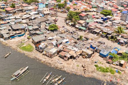 Slums in Manila, a top view. Houses of poor people and boats in poor areas. Sea pollution by household waste. Plastic trash on the beach.