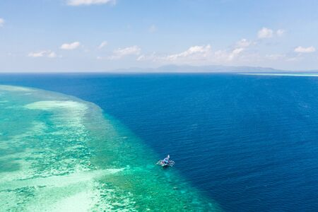 Large coral reef, top view. Tourist boat near the atoll. Seascape in the Philippines in sunny weather. Reklamní fotografie - 131333532