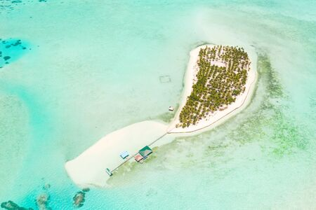 Seascape with a paradise island. Onok Island Balabac, Philippines. A small island with a white sandy beach and bungalows. Philippine Islands.