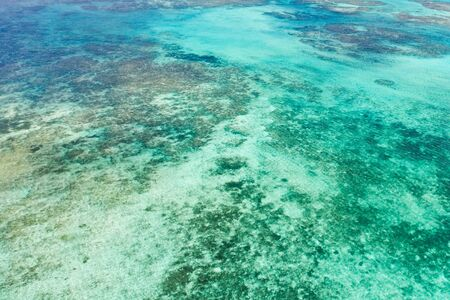 Bright lagoon with clear water and corals, top view. Sea surface above the sea atoll. Seascape.