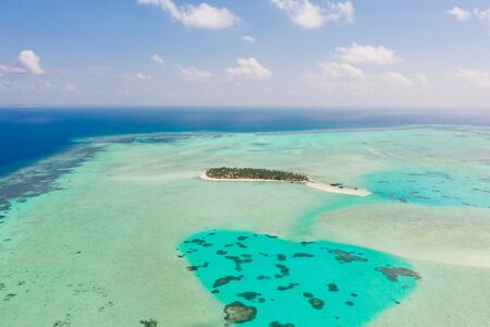 Onok Island Balabac, Philippines. The island of white sand on a large atoll, view from above. Tropical island with palm trees. Seascape with a paradise island.