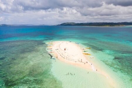 People relax on a tropical island and swim in the lagoon. Naked Island, Siargao. Tourists came to the white island in boats. White sandy island.