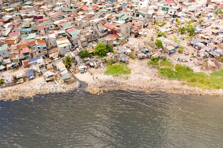 Slums in Manila, a top view. Sea pollution by household waste. Plastic trash on the beach.