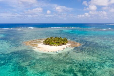 Guyam island, Siargao, Philippines. Small island with palm trees and a white sandy beach. Philippine Islands.