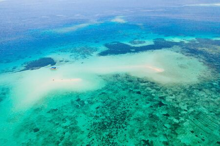 Arrecife de coral con agua turquesa y bancos de arena. Gran atolón con hermosas lagunas. Los turistas se relajan en el agua tibia del mar. Mar tropical, vista desde arriba.
