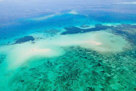 Korallenriff mit türkisfarbenem Wasser und sandigen Untiefen. Großes Atoll mit schönen Lagunen. Touristen entspannen sich im warmen Meerwasser. Tropisches Meer, Ansicht von oben.