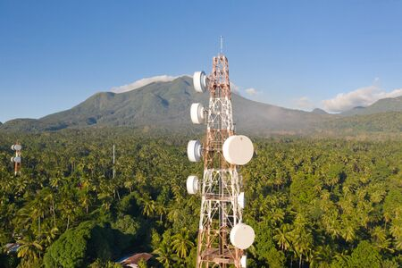 Telecommunication tower, communication antenna on Camiguin Island, Philippines. Repeaters on a metal tower. Landscape with hills and rainforest, view from above. Tower with repeaters.