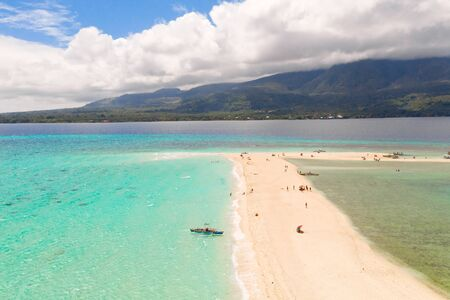 white beach overlooked by volcanos on camiguin island near mindanao in the philippines. Tourists rest on the white sandy island, view from above. Banco de Imagens