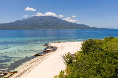 White sandy beach on the island of Mantigue, Philippines. View of the island Camiguin. White sand beach and boats.