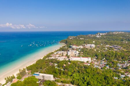 Island Boracay, Philippines, view from above. White beach with palm trees and turquoise lagoon with boats. Buildings and hotels on the big island.