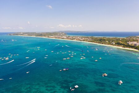 Many tourist boats near the island of Boracay. Seascape in the Philippines in sunny weather, view from above. A large densely populated island with hotels and a white beach.