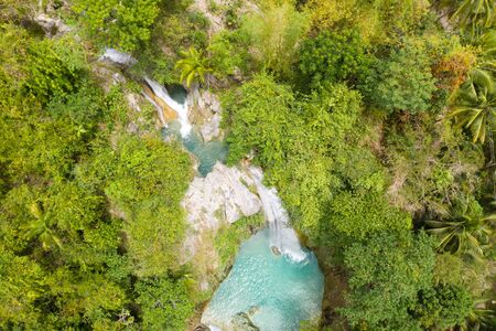 Beautiful waterfall in green forest, top view. Tropical Inambakan Falls in mountain jungle, Philippines, Cebu. Waterfall in the tropical forest. Pure water in the jungle. Stock Photo