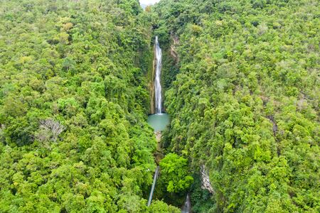 Waterfall in the jungle. Mantayupan Falls, view from above. Mantayupan Falls is one of the highest waterfalls in Cebu. The second level of the waterfalls has 98 meters high. Stock Photo