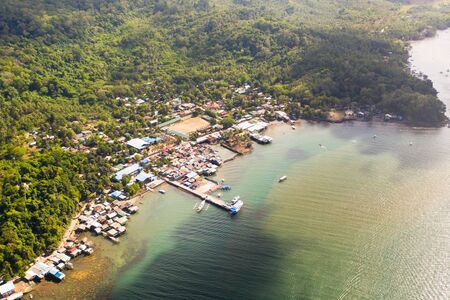 Balabac port. Houses on the water and various boats in the bay, view from above. Port town in the Philippines.