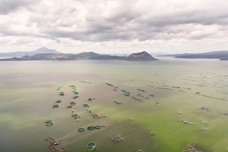 Lake Taal with a volcano and fish cages on a fish farm, top view. Luzon, Philippines Tropical landscape, mountains and volcano in the lake.