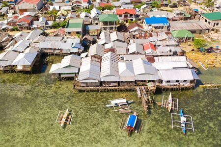 Dapa city, Siargao, Philippines. Houses on stilts, fishing village top view. Houses of local residents on the beach.