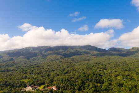 Mountain landscape on the island Camiguin, Philippines. Thick rainforest on the hills in sunny weather. Big tropical island with volcanoes. Reklamní fotografie