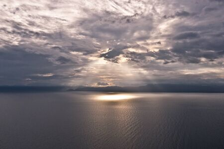 Clouds and rays of sun above the sea. Bright light with sun rays and heavy clouds above the sea. Seascape with dramatic sky.