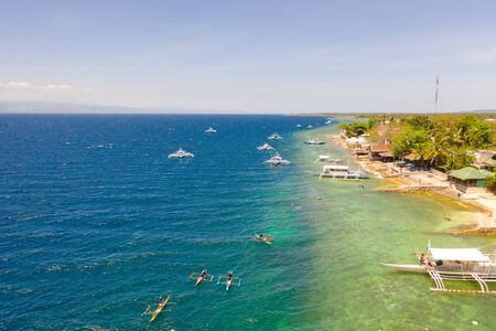 Coast of Cebu island, Moalboal, Philippines, top view. Boats near the shore in sunny weather. Seascape with coral reef near the shore. Reklamní fotografie
