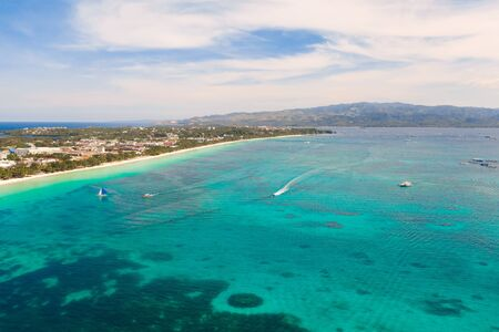 Tourist boats off the coast of the island of Boracay, Philippines, aerial view. Big island with hotels and a white beach. Seascape with a beautiful coast. Reklamní fotografie
