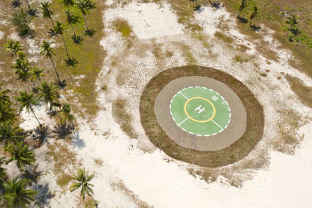 Helipad on a tropical island. Balabac, Palawan, Philippines. Helipad among the palm trees on a tropical island, top view.