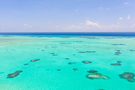 Sea water with lagoon and reefs, water background. Seascape with clear water. Large atoll with lagoon.