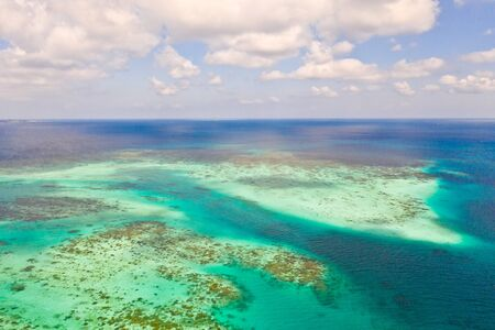 Coral reefs and atolls in the tropical sea, top view. Turquoise sea water and beautiful shallows. Philippine nature.