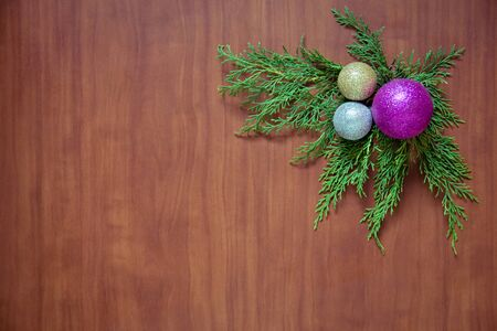 Christmas wooden background with fir branches and balls. New Years decoration.