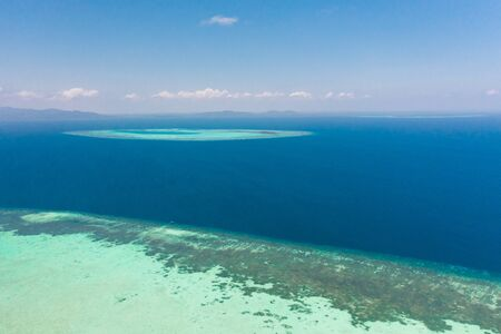 Atoll and blue sea, view from above. Seascape by day. Turquoise and blue sea water.