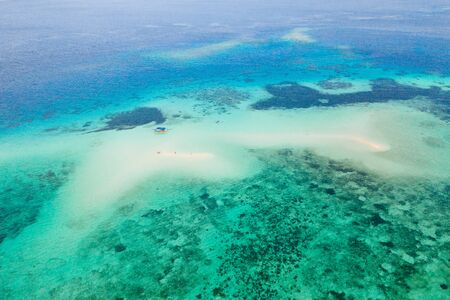 Coral reef with turquoise water and sandy shoals. Large atoll with beautiful lagoons. Tourists relax in the warm sea water. Tropical sea, view from above.