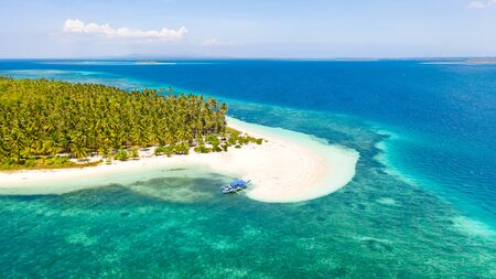 Tropical island of white sand with coconut trees. Boat with tourists on a beautiful beach, aerial view. Seascape, nature of the Philippine Islands.