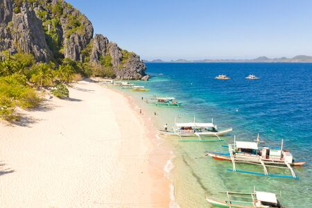 aerial view island with tropical sandy beach and palm trees. Malajon Island, Philippines, Palawan. tourist boats on coast tropical island. Summer and travel vacation concept. beach and blue clear sea water Reklamní fotografie