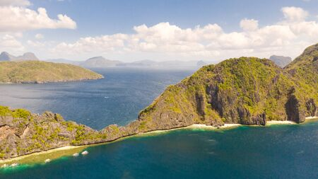 Seascape with tropical islands. El Nido Palawan National Park Philippines. Rocky islands covered with forest. Small lagoons with white beaches. Boat tours between the islands.