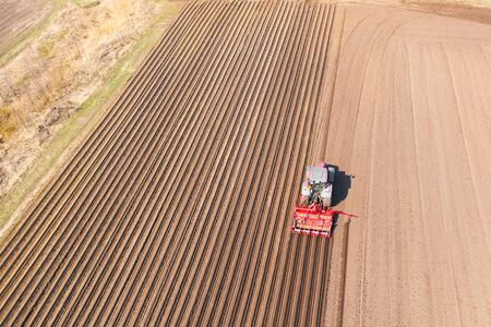 Tractor with disc harrows on farmland, top view. Tractor cuts furrows in a plowed field. Preparing the field for planting vegetables. Agricultural work with a tractor.