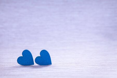 Wooden hearts on beautiful background. Two hearts, background for greetings on Valentines Day. Blue hearts.
