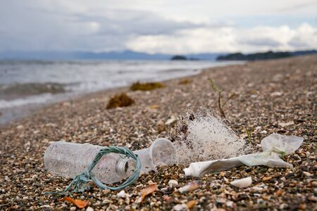 Beach pollution. Plastic bottles and other trash on sea beach. Ocean pollution. Plastic trash on the seashore.