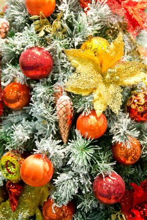 Christmas tree decorations. red christmas ball hanging on green pine with red and gold ornaments and lights.