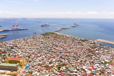 Port in Manila, Philippines. Sea port with cargo cranes. Cityscape with poor areas and business center in the distance, view from above. Asian metropolis. Stockfoto