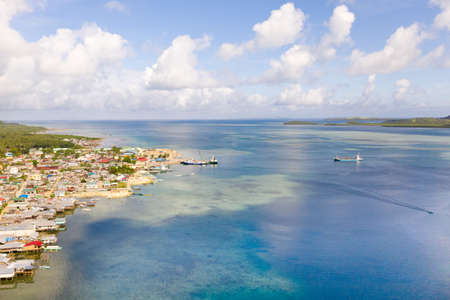 Sea port in the city of Dapa, Philippines. Fishing village and ships, view from above. Seascape in sunny weather.