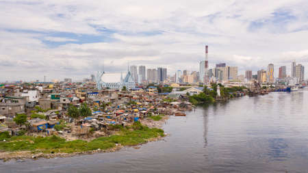Slums of poor people on the background of a big city. The city of Manila, poor and poor areas. Contrast social strata.