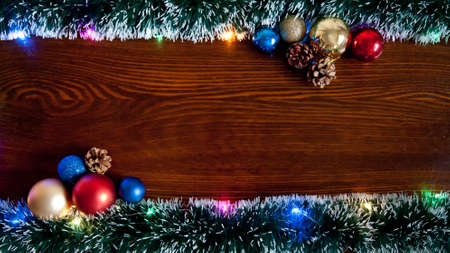 Christmas background, a table decorated with Christmas garland .With New Year and Christmas. Christmas rustic background - old wood with lights and free text